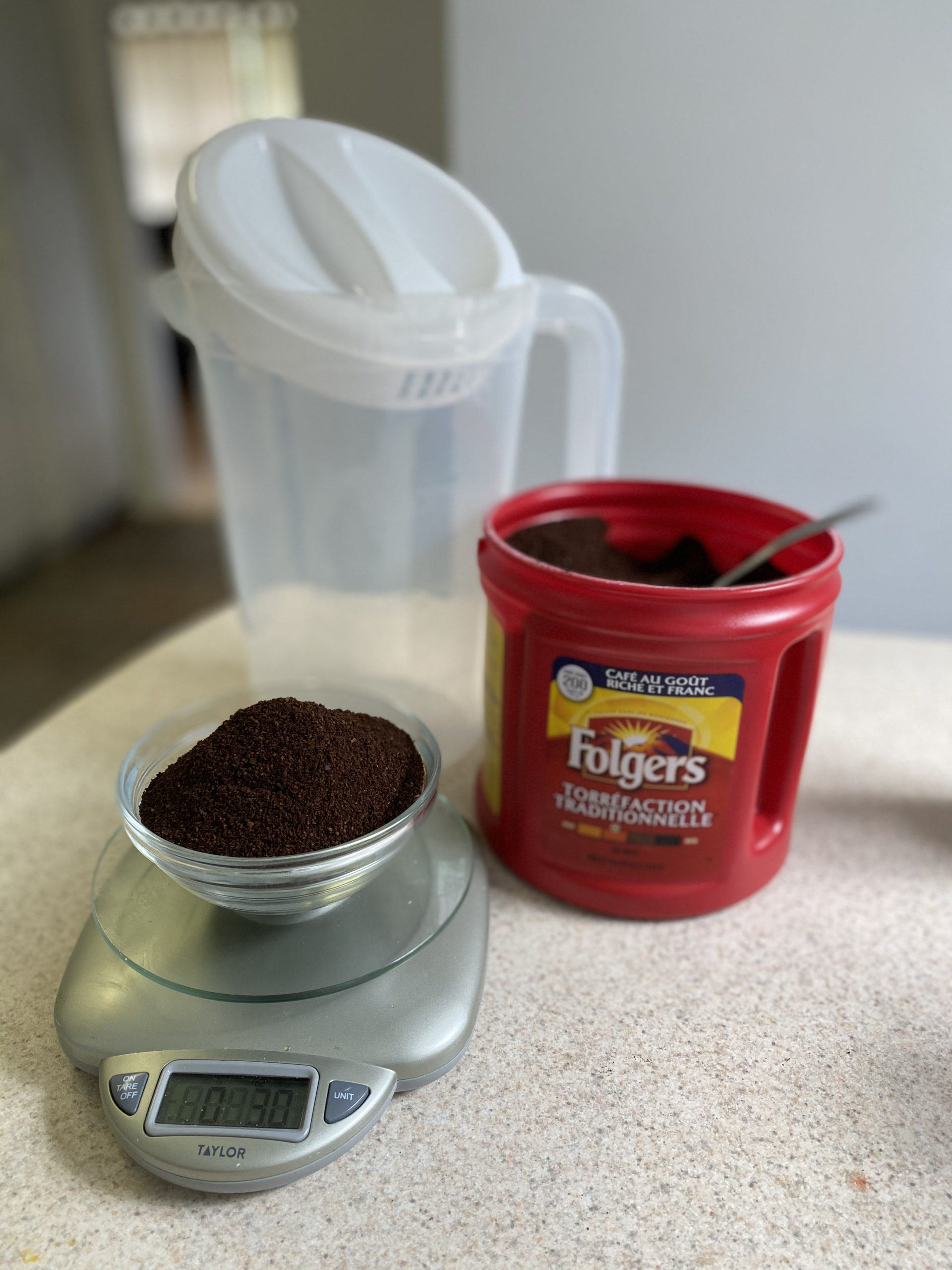 All of the ingredients for a cold brew coffee recipe being weighed out on a scale. A container of Folger's is in the background