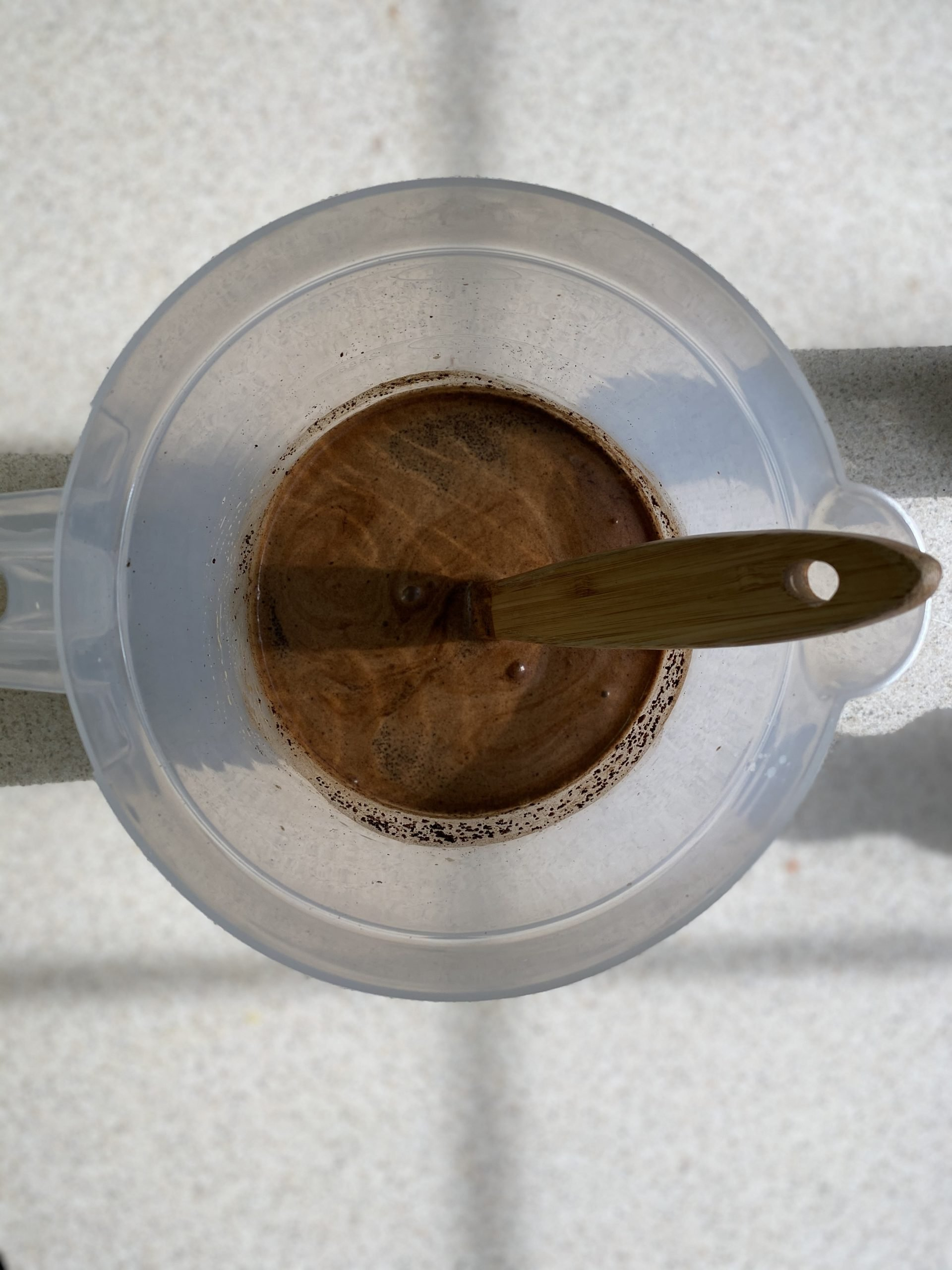 Preparing Coffee Grounds in a large container with a wooden spoon