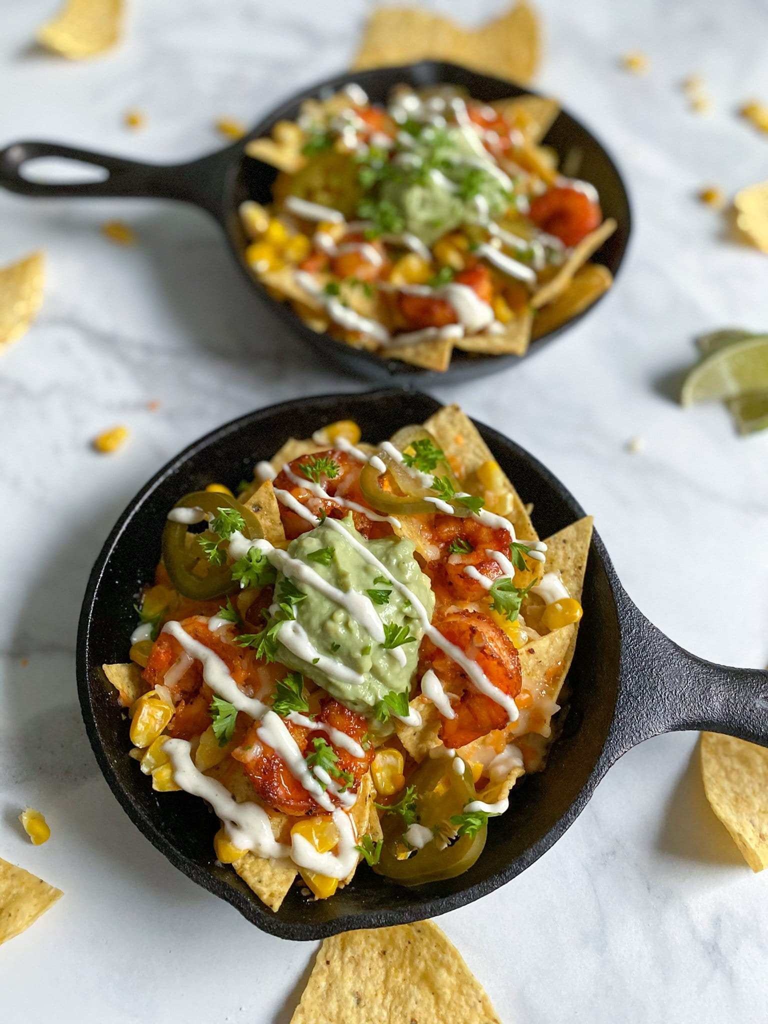 Two cast iron pans filled with honey shrimp nachos, topped with corn, guacamole and a homemade creamy cumin lime dip.