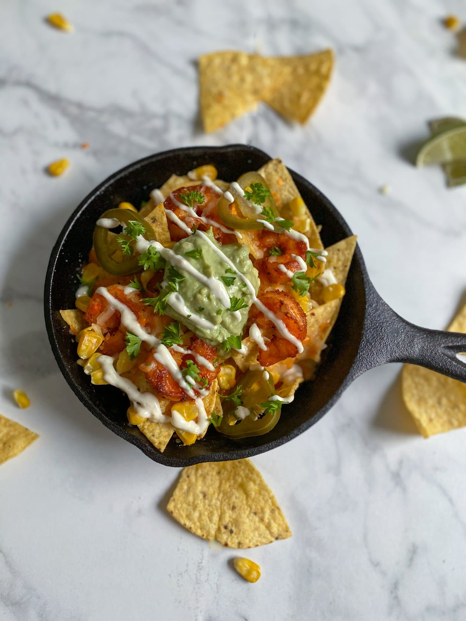 A single cast iron pan filled with honey shrimp nachos and all fixings like sauces, guacamole, corn and pickled jalapenos.