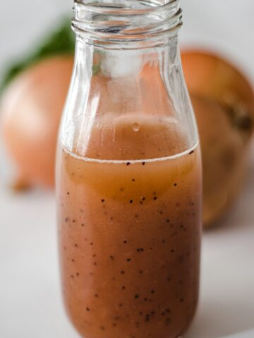 A jar of sweet onion sauce with 3 onions and parsley in the background