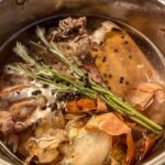 A pot filled with water and broth ingredients