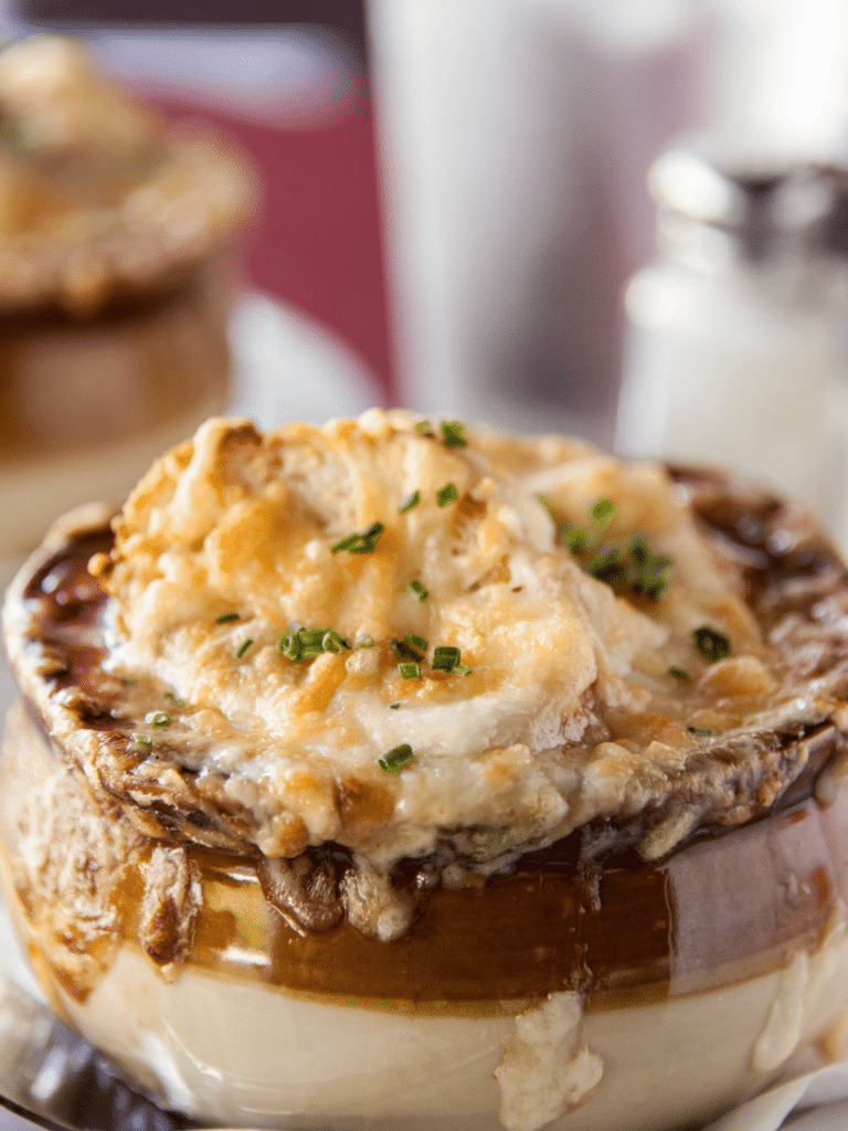 A close up shot of french onion soup with melty cheese on top