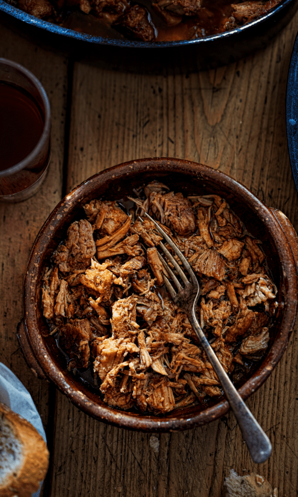 A big bowl of Ontario Pulled Pork on a wooden table with a fork across the bowl diagonally.