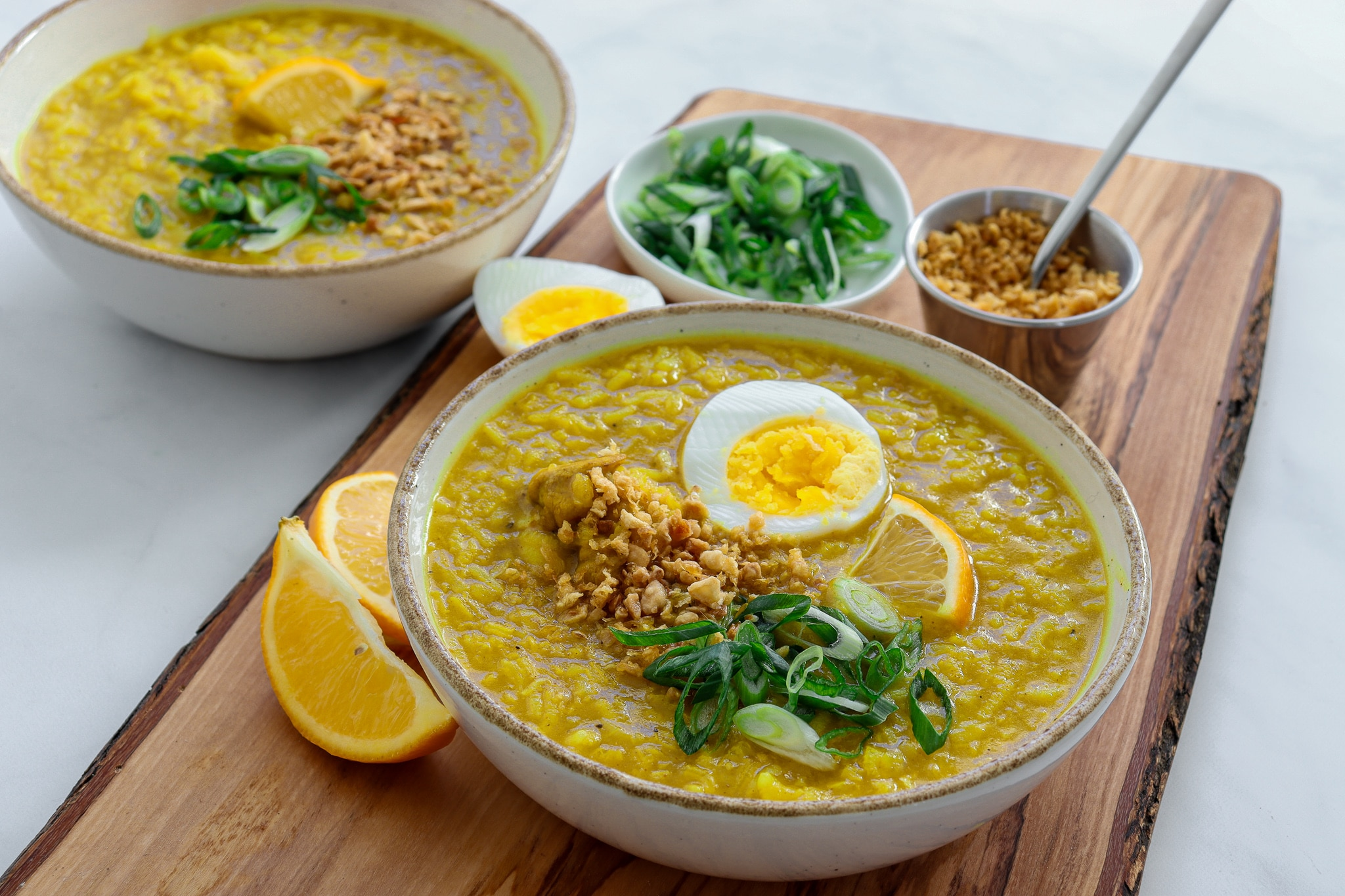 2 bowls loaded with a rich Arroz Caldo recipe - topped with a hard boiled egg, green onion, crispy fried garlic and a lemon wedge.