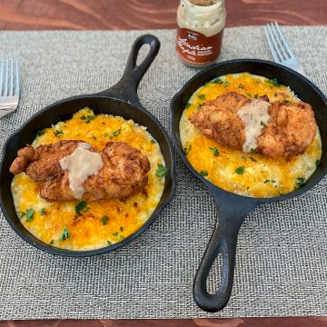 2 mini cast irons filled with Sriracha Fried Chicken Mac and Cheese and Maple Butter with a jar of maple butter and two forks in the frame
