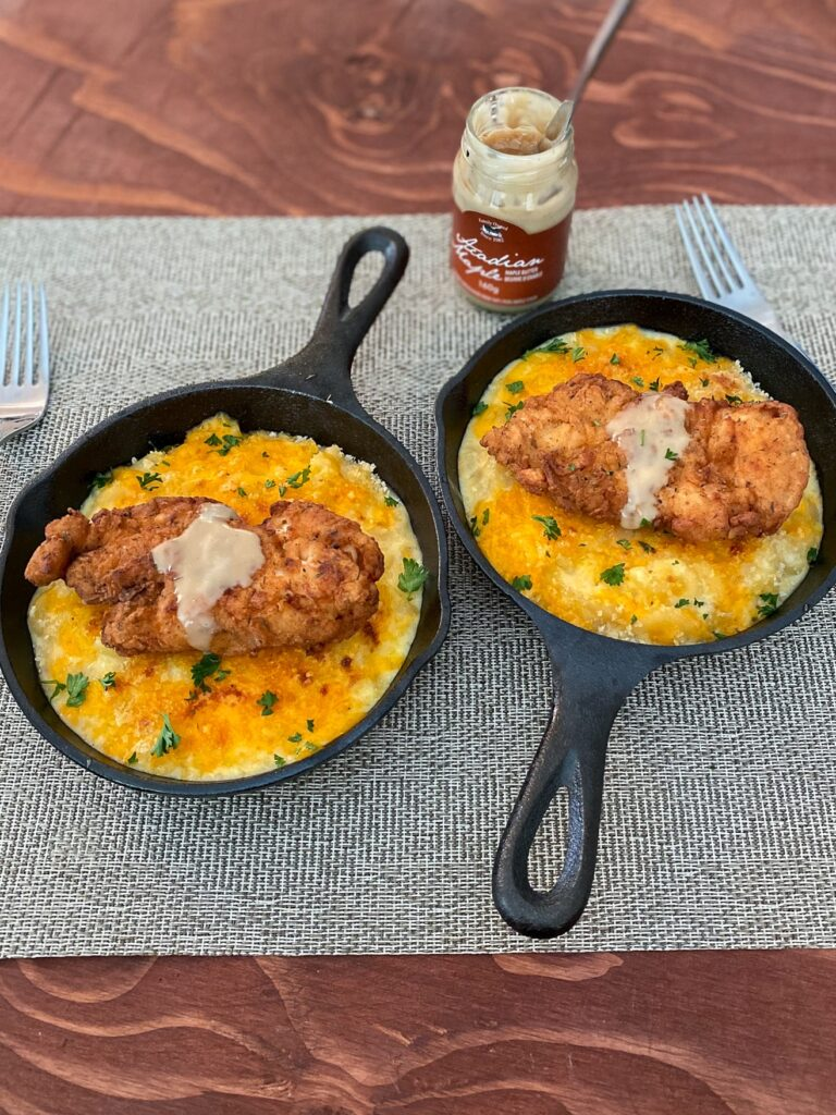 2 mini cast iron pans are filled with Mac and cheese and topped with fried chicken and maple butter. A bottle of maple butter and 2 forks are in the background.