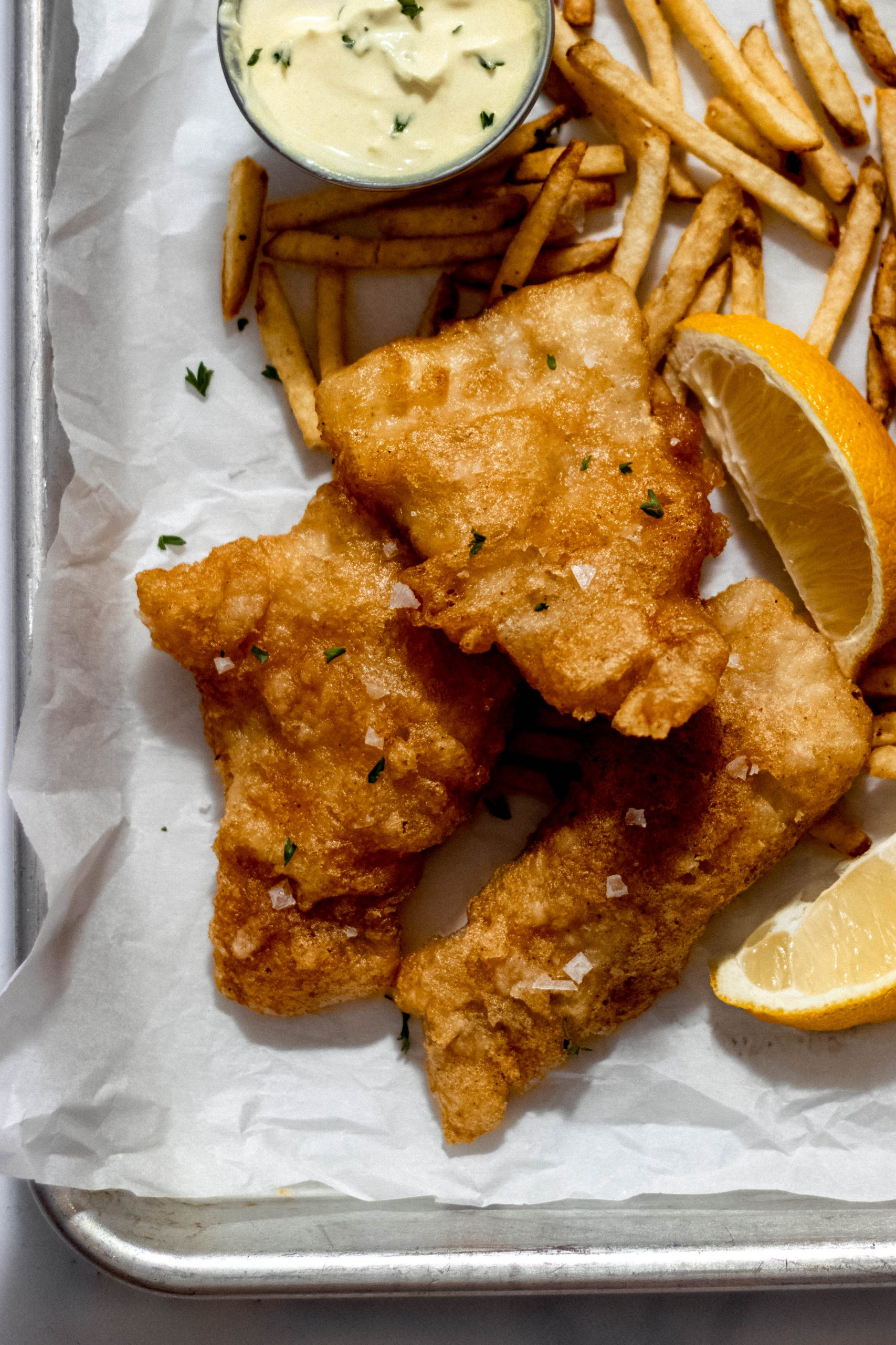 beer battered haddock, lemon wedges and chips on a parchment paper lined baking sheet