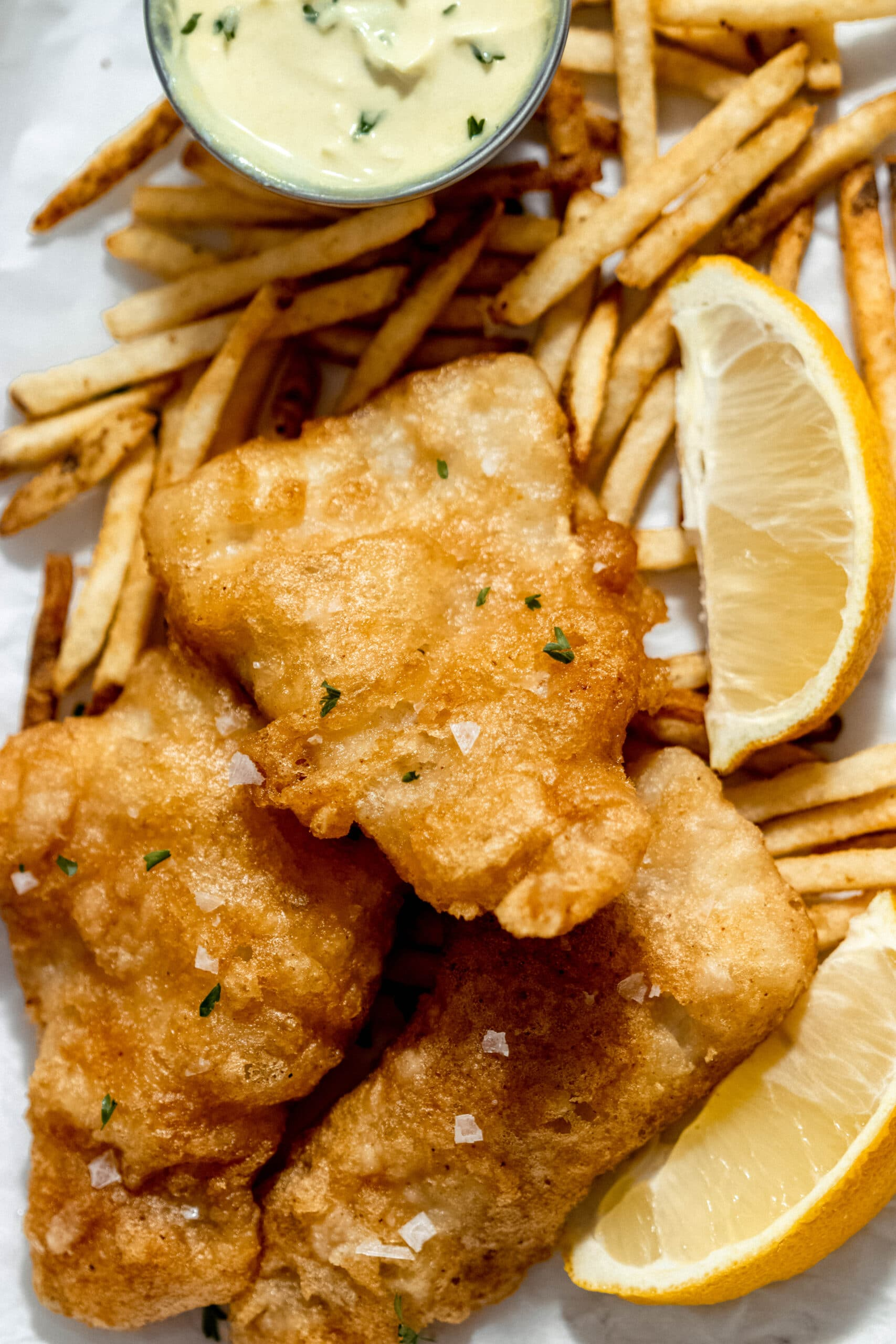 a close up shot of beer battered haddock with chips
