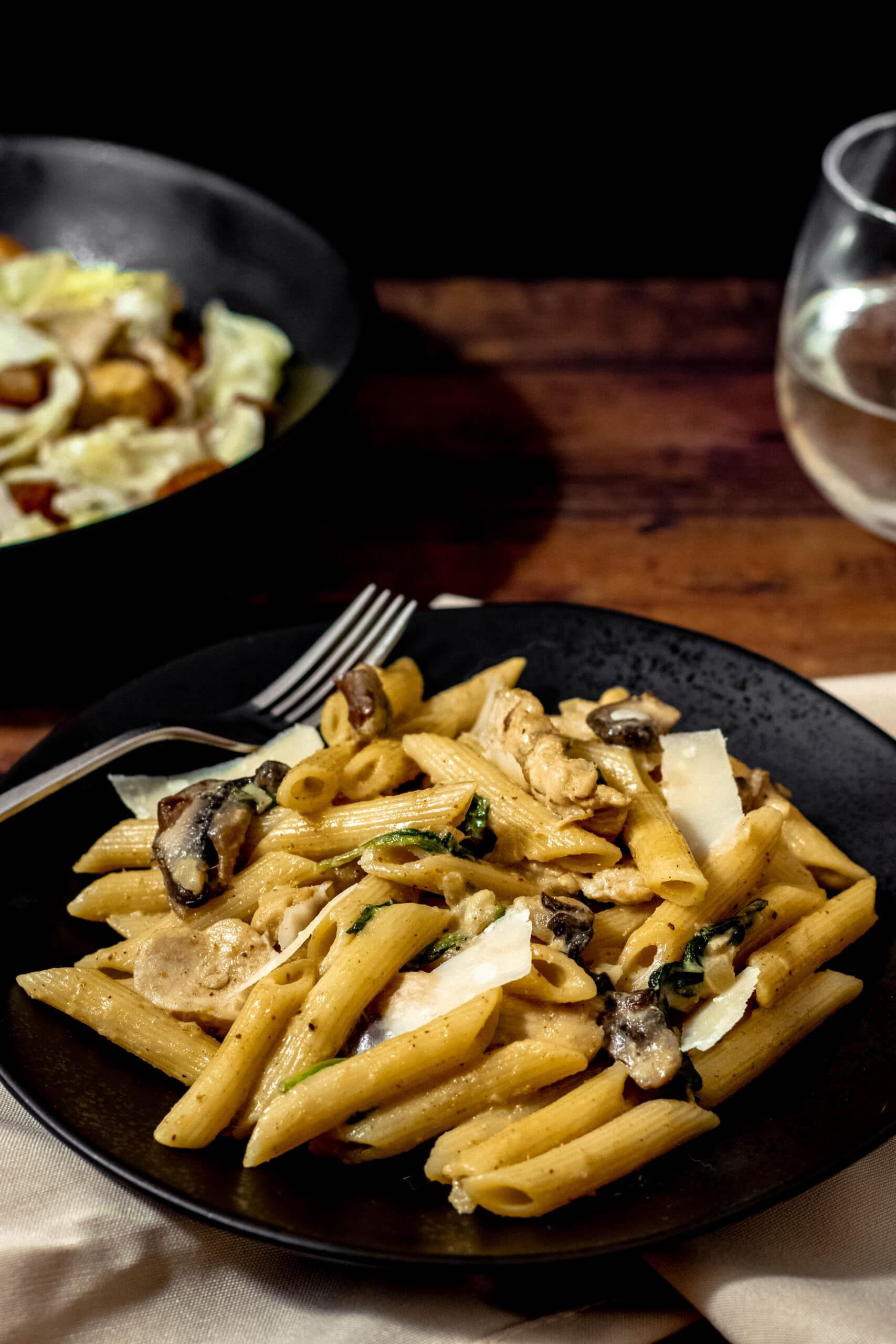 A bowl of maple curry penne on a wooden table with a glass of wine and side salad in the background