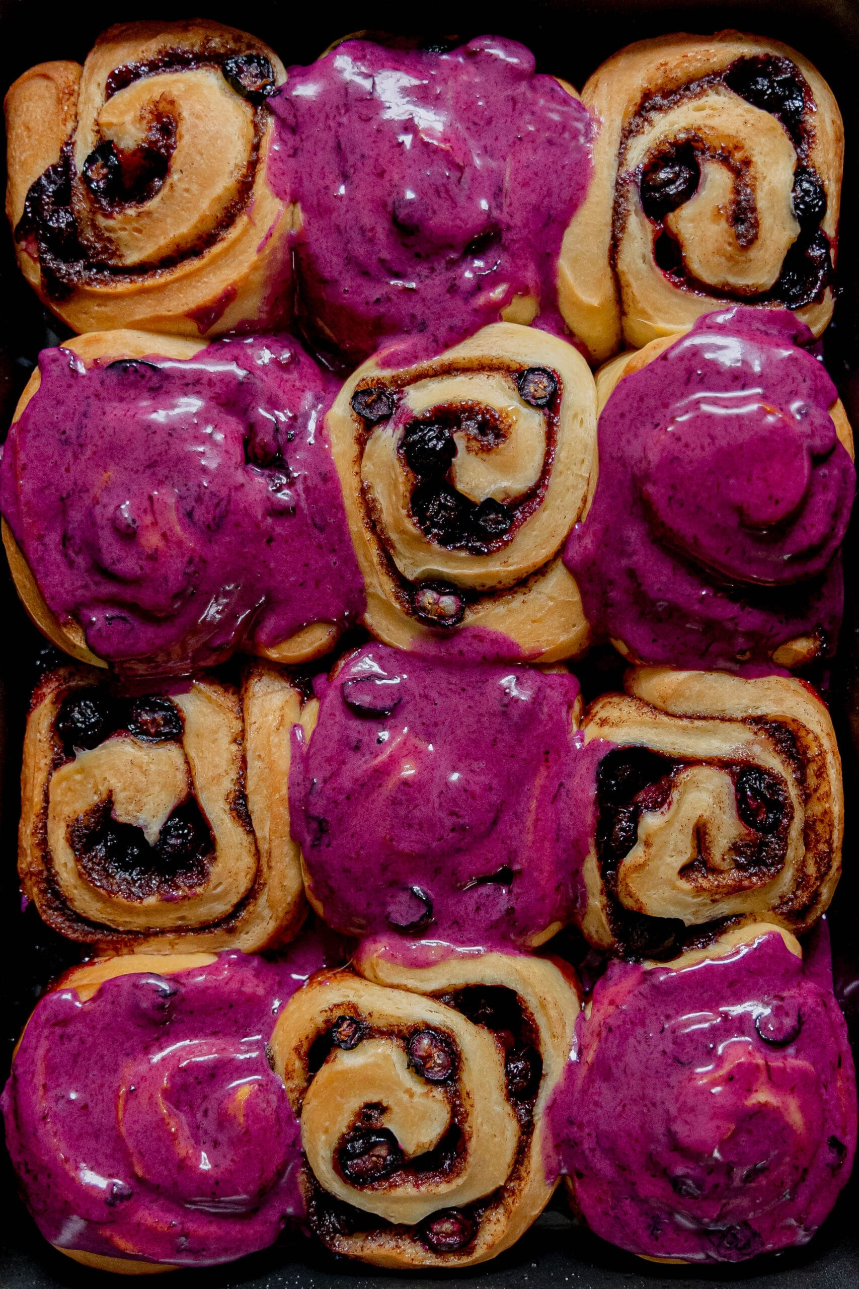 Blueberry cinnamon rolls, half frosted with rich purple blueberry icing and half bare