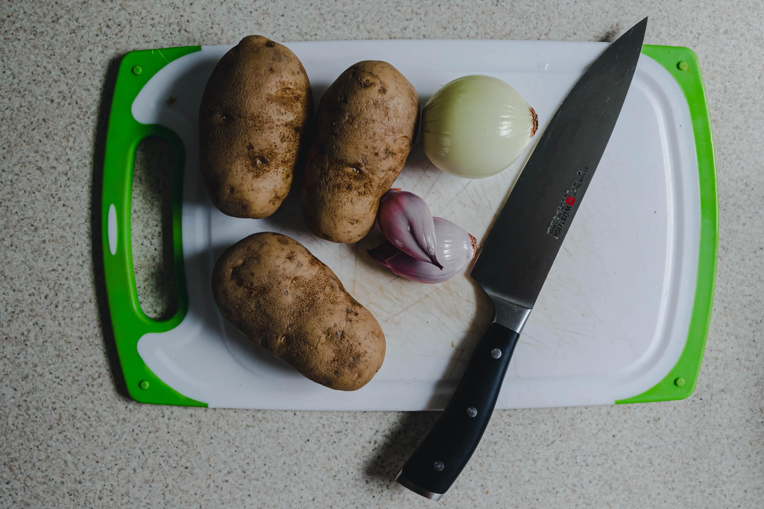 Potatoes an onion and a shallot on a cutting board with a Wusthof knife