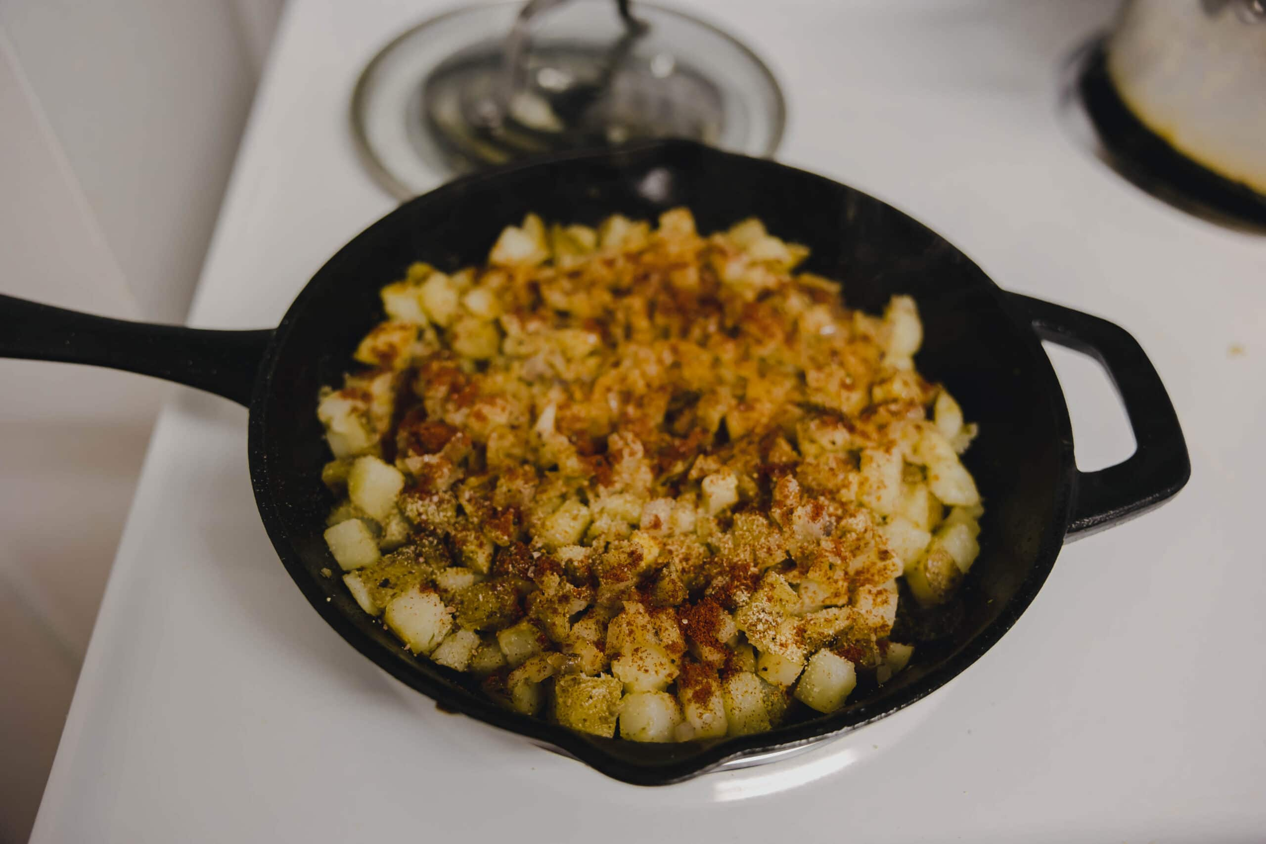 The diner style home fries, partially cooked, in a cast iron pan with seasonings on top