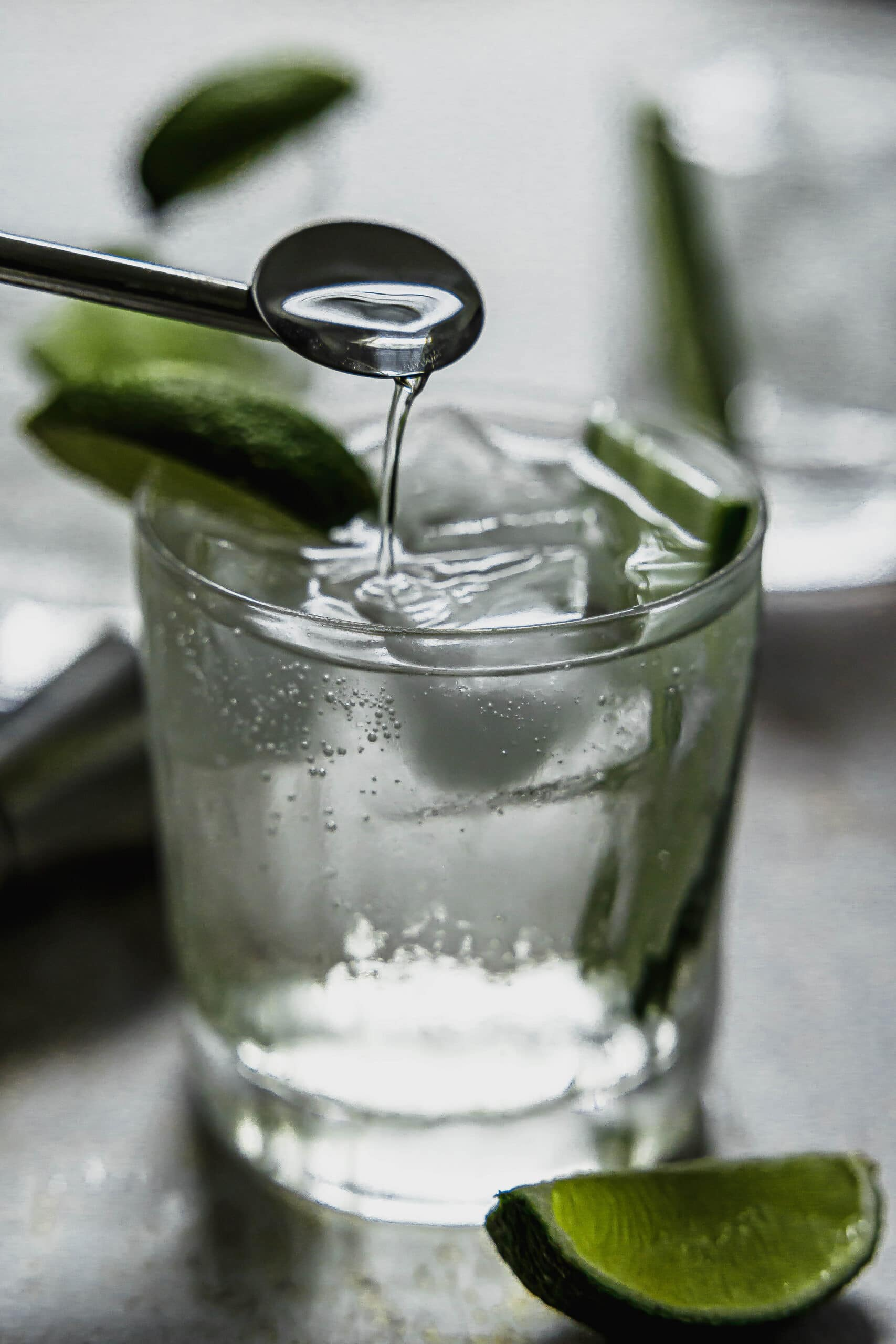 A stir spoon dripping gin and tonic into the glass after stirring.