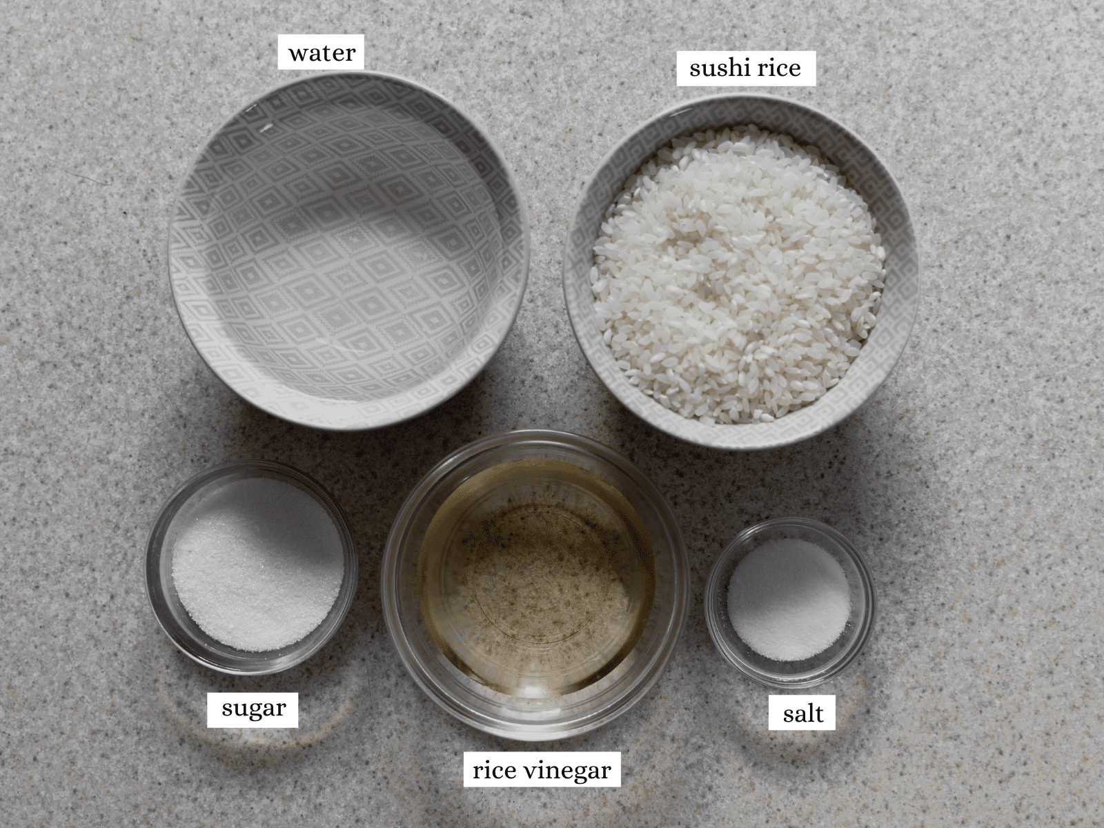 All of the ingredients needed for the recipe - water, sushi rice, sugar, rice vinegar and salt.
